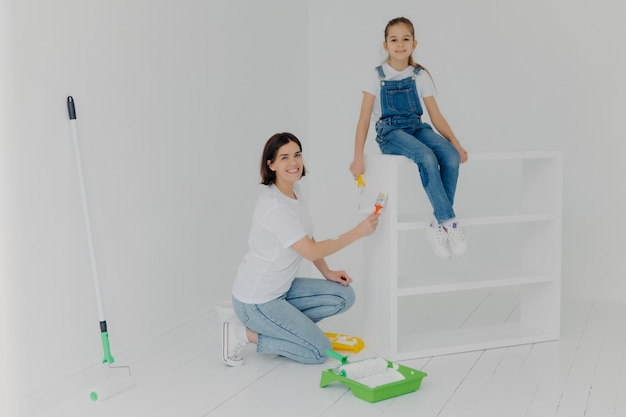 Il colpo della madre adorabile e la piccola figlia lavoratrice dura posano nella stanza vuota