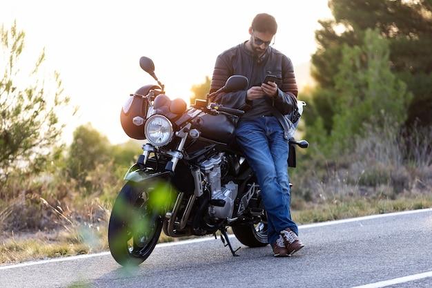 Inquadratura di un motociclista che parla al telefono con l'assicurazione della sua moto dopo aver subito un guasto sulla strada.