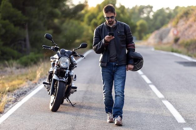 Inquadratura di un motociclista che cammina per strada mentre usa il cellulare dopo aver subito un guasto sulla strada.