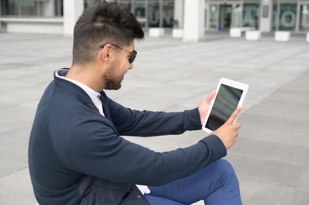 Colpo di uomo che usa tablet con schermo vuoto su strada