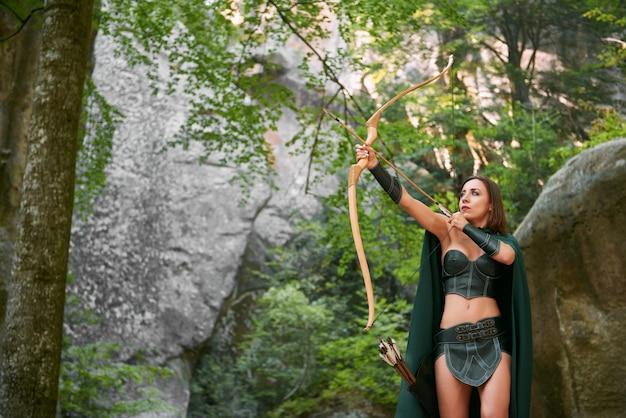 Sparato di una caccia femminile matura dell'arciere di amazon nel legno con il costume cosplay tribale tradizionale del carattere di storia della tribù del cacciatore della natura all'aperto del copyspace delle frecce e dell'arco.