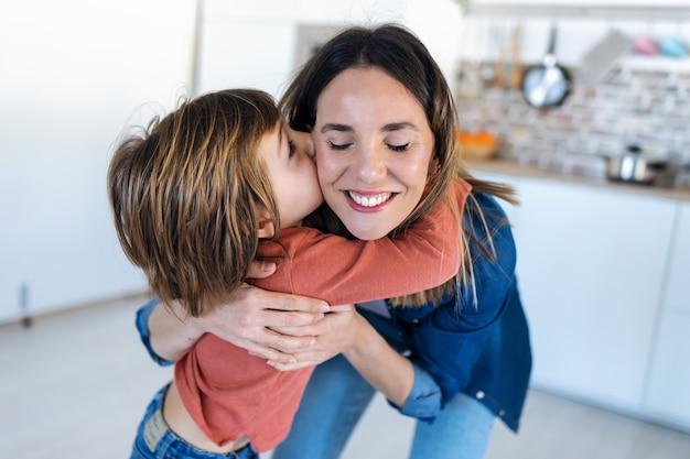 Colpo di bel ragazzo che bacia sua madre mentre si trova in cucina a casa.