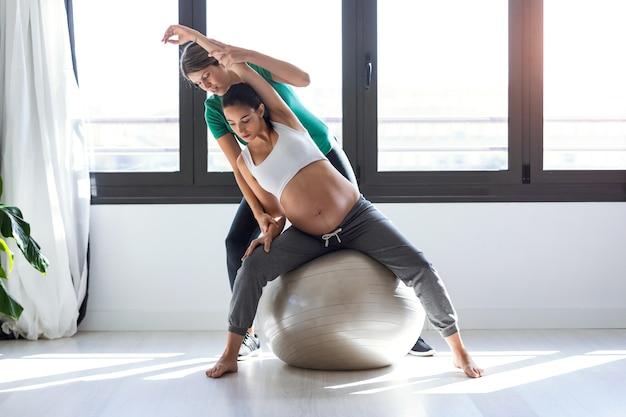 Colpo di fisioterapista che aiuta la bella donna incinta a fare esercizi di pilates con la palla che si prepara al parto.