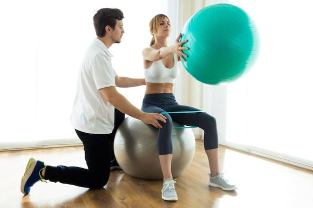 Colpo di fisioterapista che aiuta il paziente a fare esercizio sulla palla fitness nella sala fisioterapista.