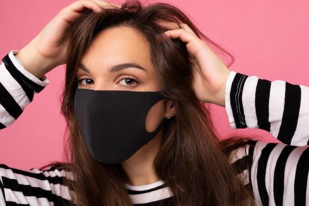 Ritratto di una giovane donna attraente bruna che indossa una maschera facciale mediale isolata su sfondo