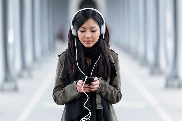 Colpo di giovane donna abbastanza asiatica che ascolta musica con il suo smartphone in strada.