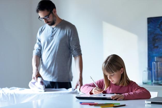 Scatto di una graziosa bambina che disegna sul taccuino mentre suo padre stira una maglietta a casa.
