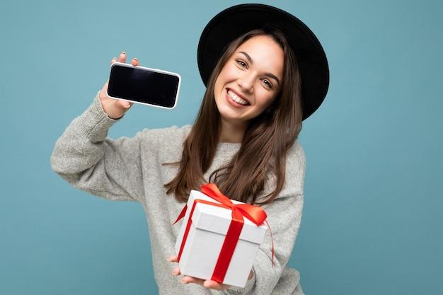 Colpo di una giovane persona di sesso femminile brunet positiva piuttosto sorridente isolata su una parete di fondo blu