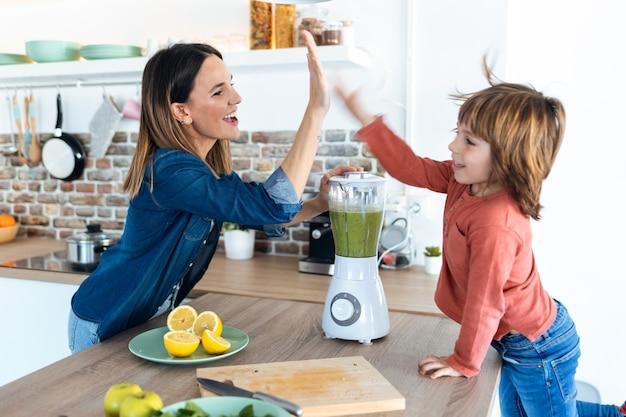 Colpo di bella giovane madre e suo figlio che danno il cinque dopo aver preparato un frullato disintossicante insieme nella cucina di casa.