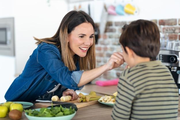 Colpo di bella giovane madre che gioca con suo figlio mentre taglia la banana in cucina a casa.