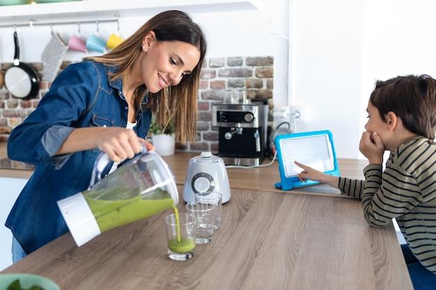 Colpo di bella giovane madre che serve succo verde detox mentre suo figlio usa la tavoletta digitale a casa.