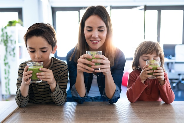 Colpo di bella giovane madre con i suoi figli che bevono frullato disintossicante in cucina a casa.