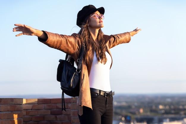 Colpo di bella giovane donna che si gode il tempo e il tramonto stando in piedi sul tetto.
