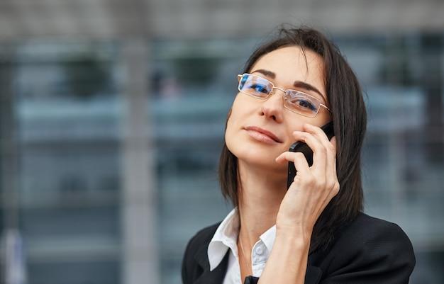 Un colpo di bella giovane donna che utilizza il suo telefono cellulare mentre si trovava in strada