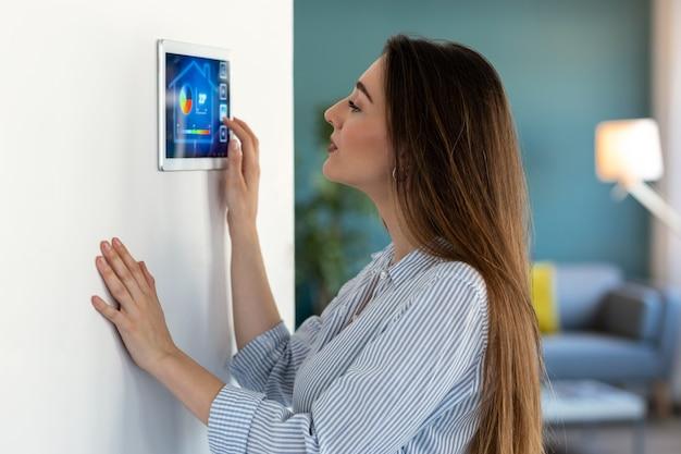 Colpo di bella giovane donna che utilizza il sistema di automazione domestica su tablet digitale per regolare la temperatura.