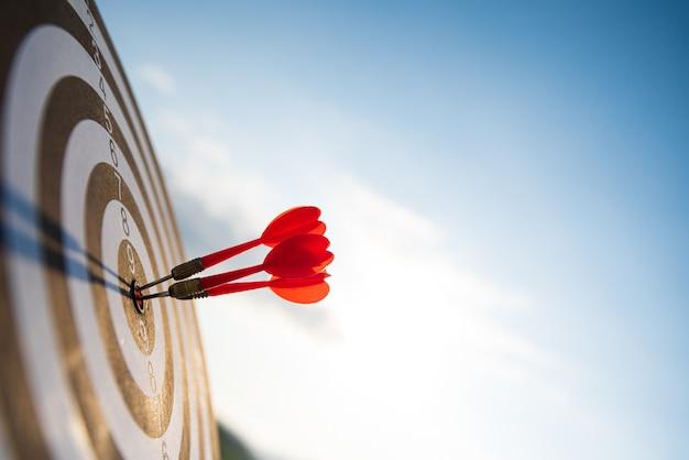 Sparato frecce rosse delle frecce nel centro dell'obiettivo sulla parete del cielo blu