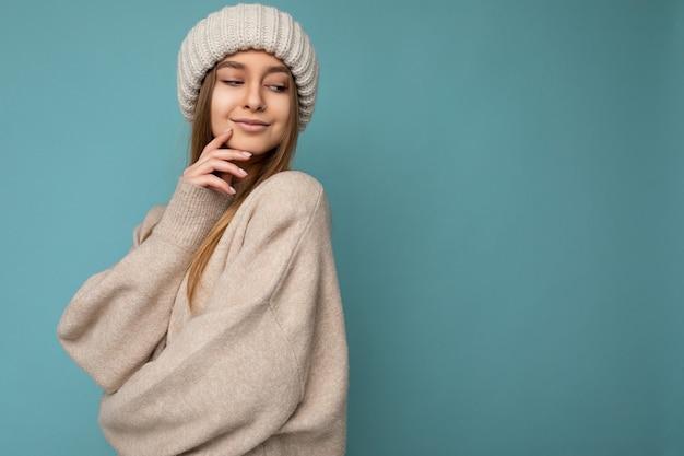 Colpo di sexy piuttosto felice giovane donna bionda scura in piedi isolato sul muro sfondo blu che indossa un maglione caldo beige e cappello beige invernale guardando verso il basso. spazio libero, copia spazio