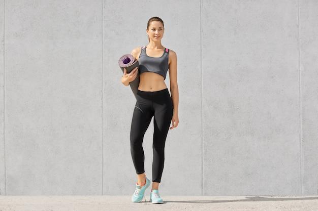 Colpo di fitness signora sportiva in top casual, leggings e scarpe da ginnastica, pronto per l'allenamento detiene materassino, isolato su grigio muro di cemento.