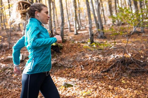 Colpo di giovane donna sportiva che corre nel parco la mattina d'autunno.