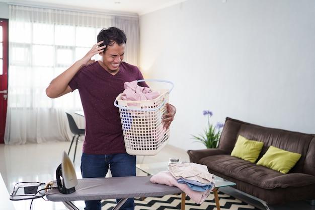 Colpo di marito stressato o uomo single impegnato con i lavori domestici, stira la camicia la mattina sulla scrivania da stiro prima del lavoro,