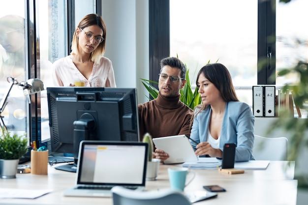Scatto di un giovane team aziendale di successo in piedi intorno al computer che fa una videochiamata nello spazio di coworking.