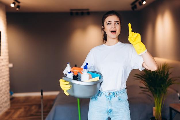 Colpo di cameriera di pulizia sorpresa in guanto giallo che tiene detersivi in soggiorno