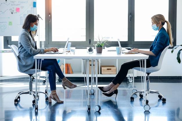 Scatto di due donne d'affari che indossano una maschera igienica mentre lavorano con i laptop nello spazio di coworking. concetto di distanza sociale.
