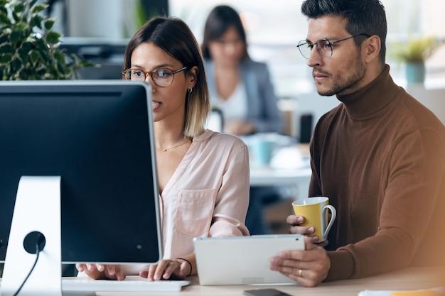 Scatto di due giovani colleghi di lavoro che lavorano insieme a un computer e un tablet digitale in uno spazio di lavoro moderno. concetto di brainstorming.