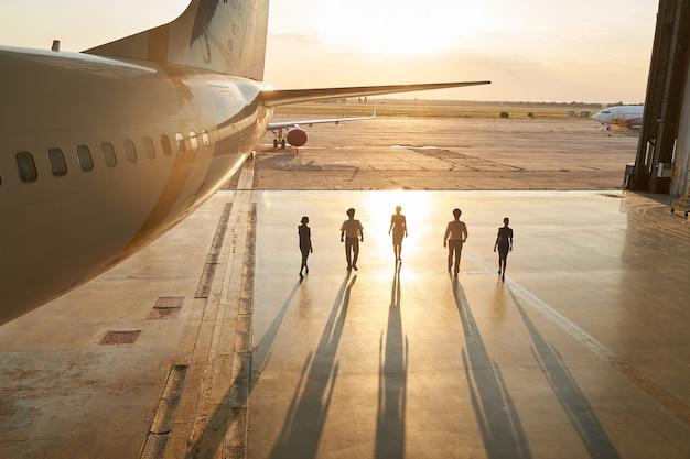 Inquadratura di piloti e hostess non identificabili che escono da un hangar al tramonto