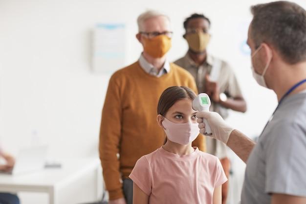 Colpo di medico irriconoscibile che controlla la temperatura della bambina che indossa la maschera e aspetta in fila in clinica o in ospedale, copia spazio