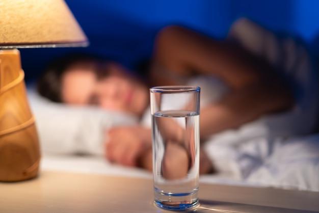Lo scatto di una vodka sullo sfondo della donna addormentata