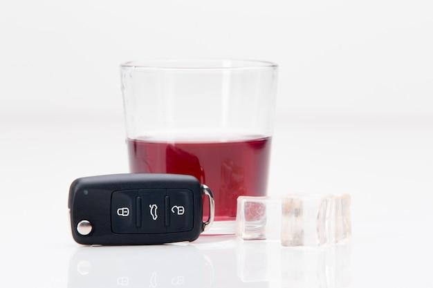Un colpo di whisky e un set di chiavi della macchina su uno sfondo bianco
