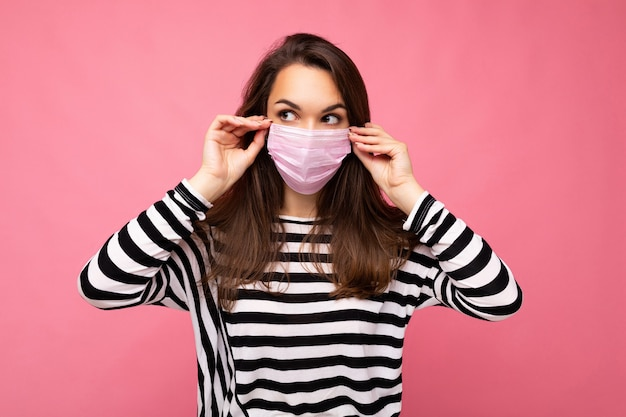 Colpo di giovane donna attraente che indossa una maschera medica