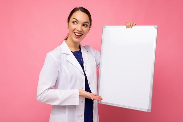 Colpo di giovane di bella sorridente felice brunet medico femminile che indossa un camice bianco medico holding