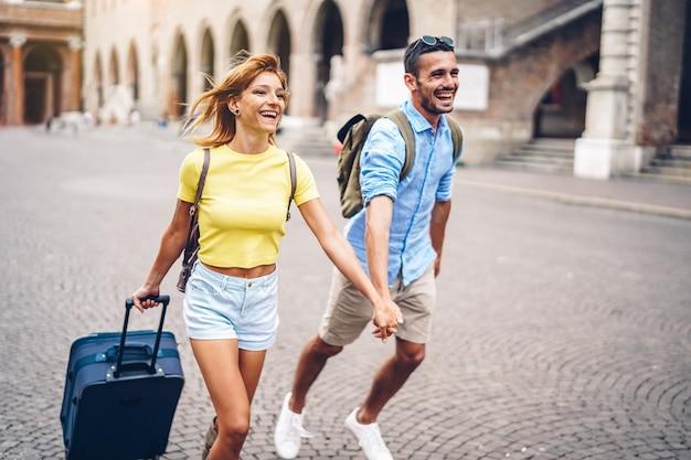 Sparato di giovani coppie che si tengono per mano e che corrono nella valigia di trasporto della città in vacanza.
