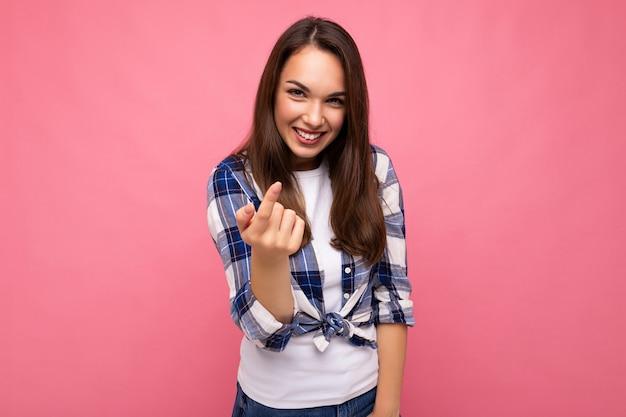 Colpo di giovane donna castana affascinante sorridente felice con emozioni sincere che indossa camicia a quadri alla moda isolata sul rosa