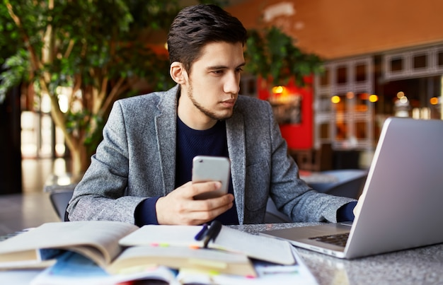 Sparato di giovane studente maschio che si siede alla tavola e che scrive sul taccuino. giovane studente maschio che studia in caffè.