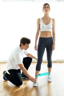Colpo di giovane fisioterapista che dà consigli alla sua paziente durante l'allenamento del corpo in una stanza di fisioterapia.
