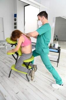 Colpo di giovane fisioterapista che massaggia la schiena della donna incinta. uomo che indossa la maschera protettiva durante la nuova normalità.