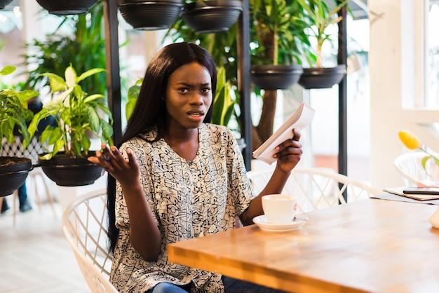 Colpo di giovane donna seduta in una caffetteria con laptop e bere caffè. ragazza afroamericana che mangia caffè caldo e fresco al caffè.