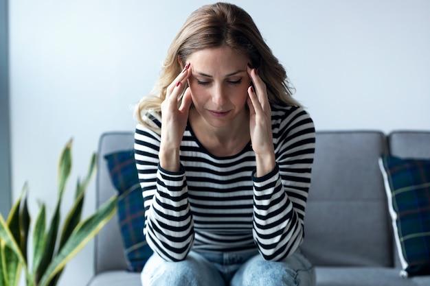 Colpo di giovane donna con mal di testa seduta sul divano nel soggiorno di casa.