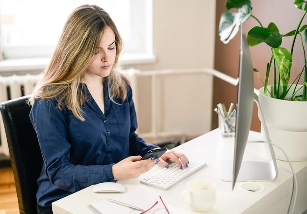 Inquadratura di una giovane donna che lavora da casa utilizzando smart phone e computer, le mani della donna utilizzando smart phone