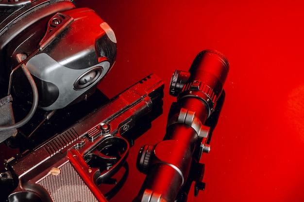 Fucile da caccia e auricolari protettivi su sfondo con luce rossa si chiudono