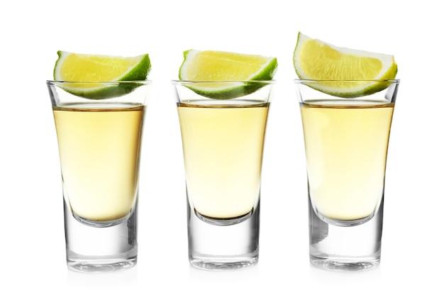 Colpi di tequila d'oro con fetta di lime in una fila isolata su bianco