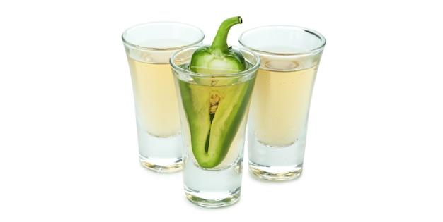Colpi di tequila con pepe isolato su sfondo bianco