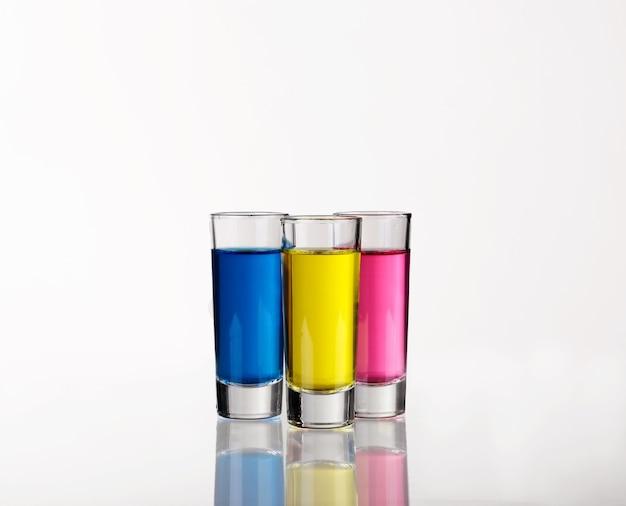 Scatti - tre bevande colorate su bianco con riflessi