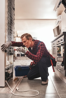 Dovrebbe essere un tecnico maschio senior attento che controlla il frigorifero
