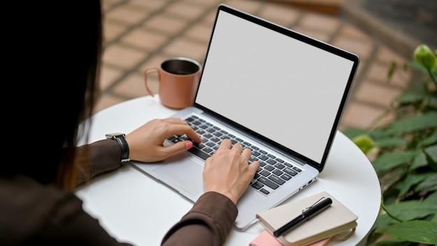 Sopra la vista del primo piano della spalla delle mani femminili che digitano sulla tastiera del computer portatile sulla tavola rotonda nel giardino al caffè