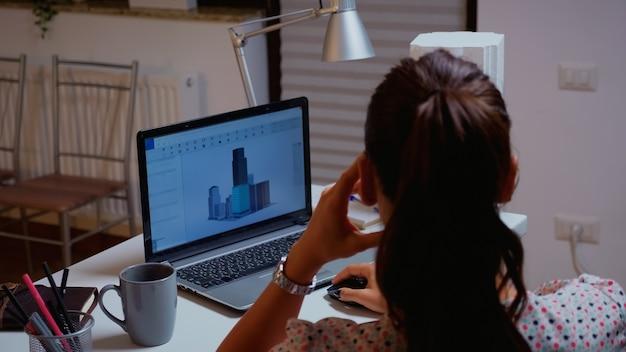 Inquadratura da sopra la spalla dell'ingegnere che lavora con il software cad su un computer desktop. designer che utilizza un concetto 3d di edifici che lavorano a distanza da casa creando e studiando un nuovo modello moderno