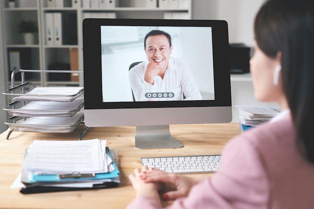 Sopra la vista della spalla della donna di affari che si siede alla scrivania e utilizzando il computer mentre si parla con il partner d'affari asiatico online